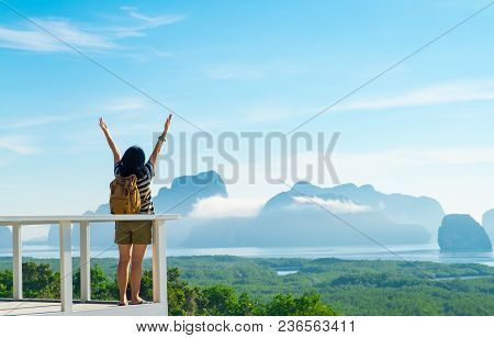 Happy Young Traveler Woman Backpacker Raised Arm Up To Sky Enjoying A Beautiful Of Nature At Mountai