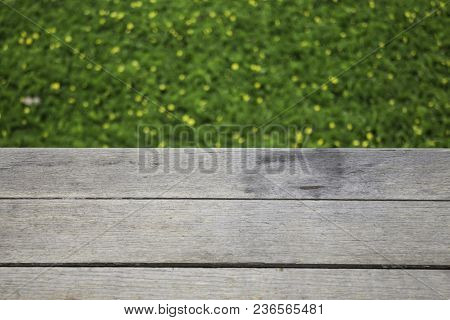 Yellow Little Flower On Green Grass With Wooden Background, Stock Photo