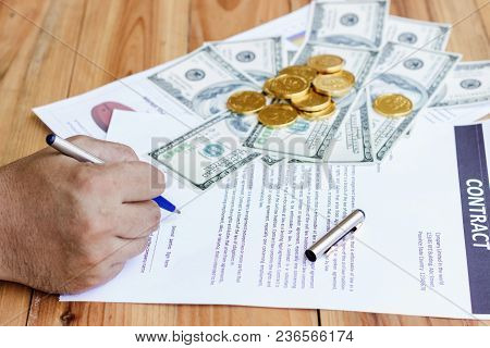 A Businessman's Hand Is Holding A Pen To Sign A Contract In A Business Deal Financials Of A Professi