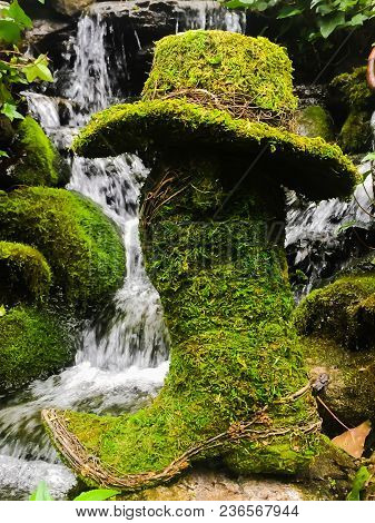 A Moss Covered Boot And Hat Sitting In Front Of A Lush Green Tranquil Waterfall