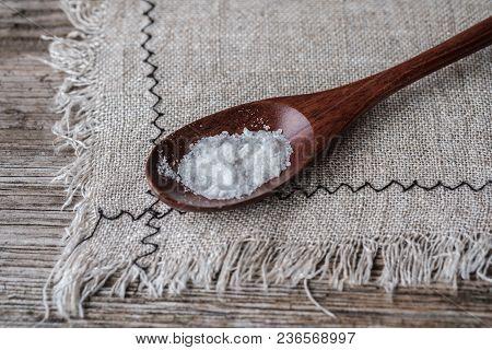 Salt In A Brown Wooden Spoon On A Grey Linen Napkin