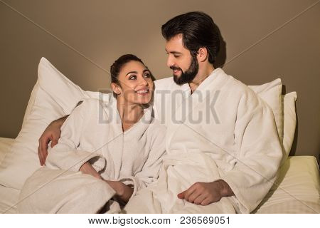 Beautiful Couple In Bathrobes Embracing In Bed Of Hotel Suite And Looking At Each Other