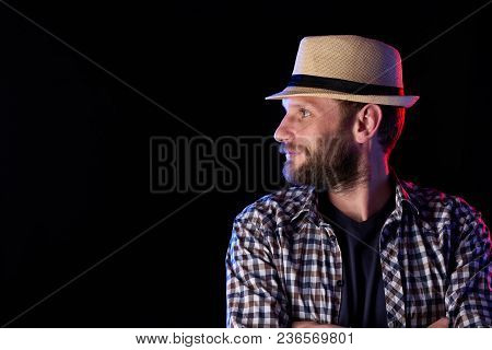 Profile Closeup Portrait Of Bearded Man Looking To The Side Wearing Fedora Hat Over Dark Background,