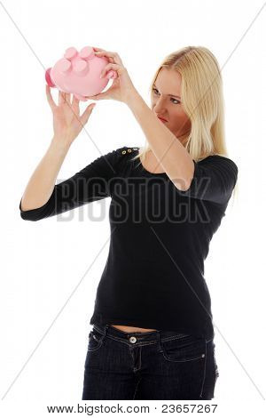 Savings concept - a woman with a piggy bank trying to get out some money - isolated over white
