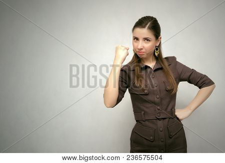 Dissatisfied Annoyed Girl Isolated On Gray Background With Copy Space. Angry Boss Woman Shakes A Fis