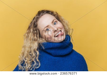 Funny Comic Curly Young Woman With Positive Expression, Shows Tongue, Has Fun With Friends, Wears Bl
