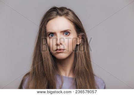 Headshot Of Beautiful Female With Blue Eyes And Pure Skin, Looks Seriously And Angrily At Camera, Ha