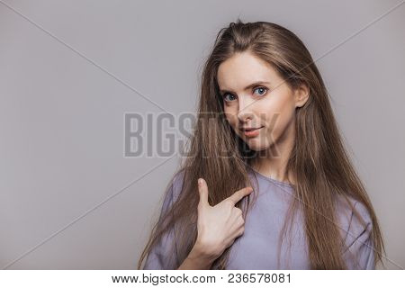 Pretty Young Woman With Dark Long Straight Hair Indicates At Herself, Has Blue Eyes, Surprised To Be