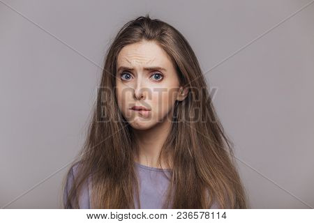 Offended Stressful Female Bites Lower Lip With Dissatisfaction, Has Sorrorful Expression, Expresses