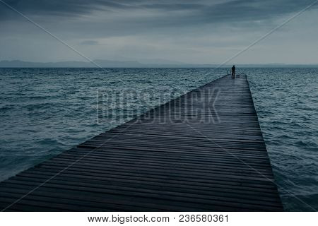 Outdoor View Of Wast Pier Acoss Ocean And Silhouete Of Unrecognizable Man Has Walk And Admires Nice