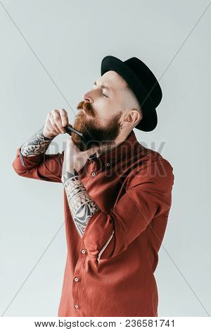 Side View Of Bearded Handsome Man Combing Beard Isolated On White