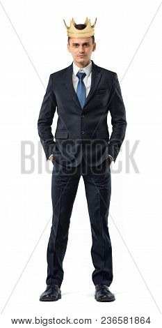 An Isolated Businessman Stands With A Golden Crown On His Head In A Front View. Business And Success