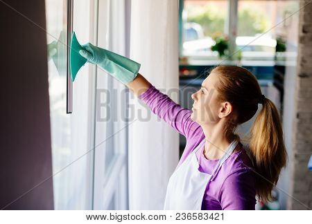 Young Woman In White Apron Cleaning Windows.