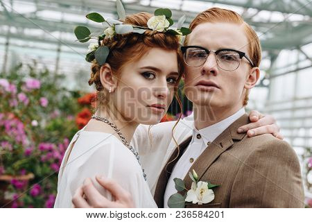 Beautiful Elegant Young Wedding Couple Embracing And Looking At Camera