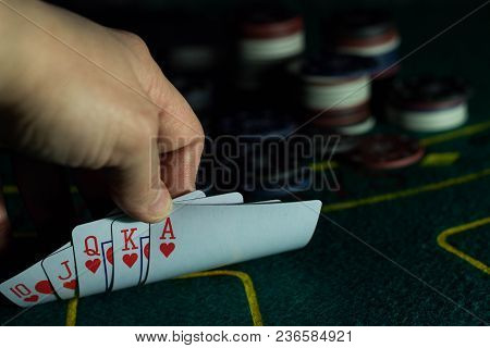 Cards In A Combination Of A Royal Flush On A Poker Table Raised By A Hand During The Game With Chips