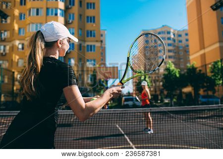 Two Women Playing Tennis Outdoor. Practicing Tennis On The Tennis Court At Sunny Day, On A City Back