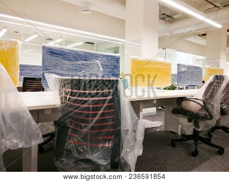 Colorful New Office With Cubicles, Chairs, Tables And Carpets. The Plastic Polythene Covers Are Stil