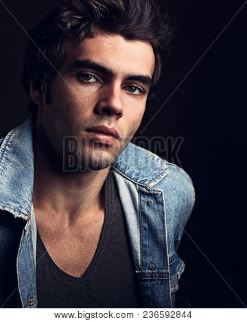 Sexy Serious Male Model Posing In Blue Jacket On Dark Shadow Background. Fashion Toned Vogue Portrai