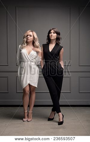 Gorgeous Fashion Ladies. Two Beautiful Brunette And Blonde Girls In Evening Black And White Classy C