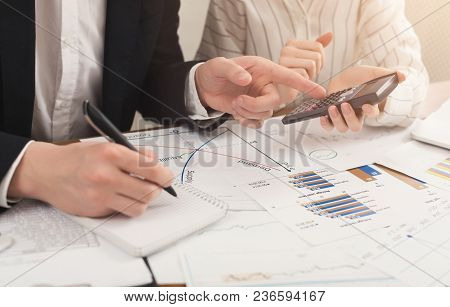 Closeup Of Business Colleagues Hands Writing Notes And Counting Account On Calculator. Financial Bac