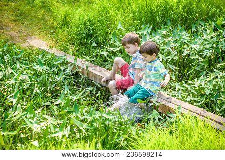 Two Cute Little Boys Sitting On A Wooden Bridge