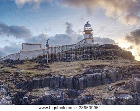 Lighthouse Building With Tower Against To Evening Sky. Popular Neist Point, Spit Of Land Isle Of Sky