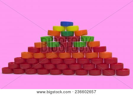 Flat Pyramid Of Colored Plastic Bottle Caps On Pink Background