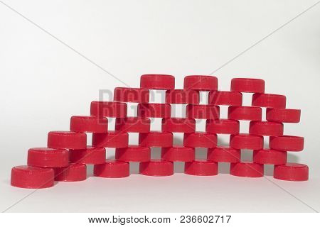 Rows Of Red Ribbed Plastic Bottle Caps Laying On Each Other. Holes Pattern