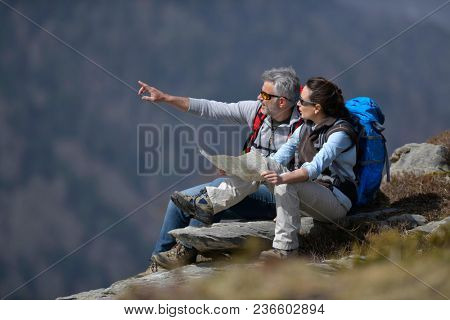 Hikers reading map and pointing at scenery