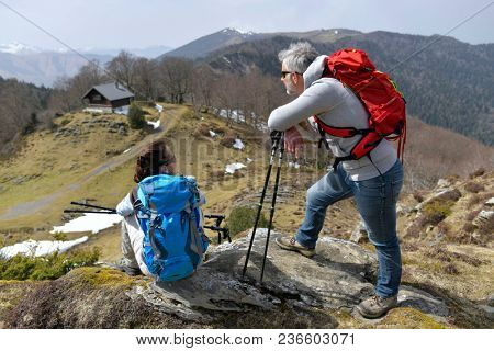 Hikers admiring mountain scenery during trekking day