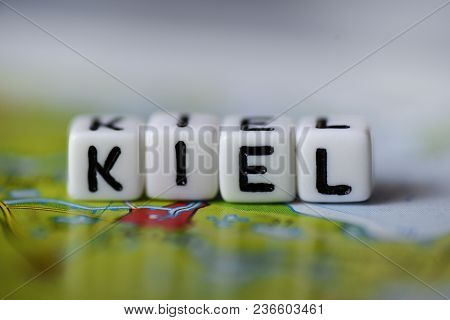 Word Kiel Formed By Alphabet Blocks On Atlas Map Geography
