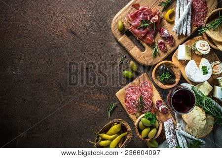 Antipasto Delicatessen - Sliced Meat, Ham, Salami, Cheese, Olives, Ciabatta And Red Wine On Dark Sto