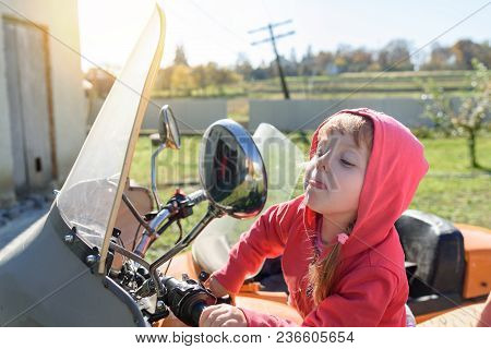 Funny Little Girl Sits On Motorcycle, Looks In The Mirror And Shows Tongue, Careless Childhood