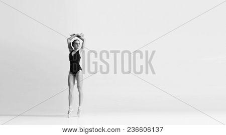 Graceful ballerina dancing in art performance.