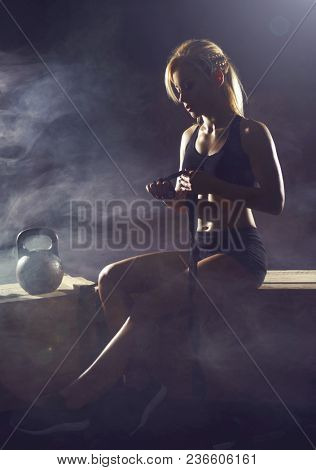 Fit and sporty young girl having a training. Dark underground gym. Health, sport, fitness concept.