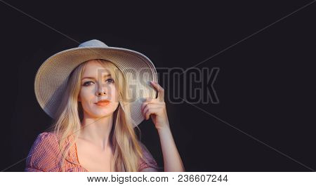 Beautiful Young Woman In Pink Dotted Summer Dress And Sun Hat Points To Copy Space, Looking At Camer