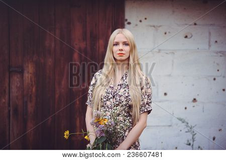 Beautiful Young Woman In A Summer Dress With Wildflowers On A Wall Background With Holes From Bullet