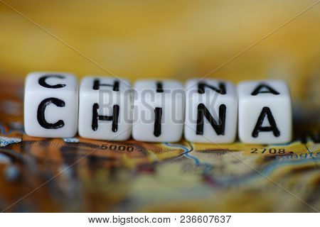 Word China Formed By Alphabet Blocks On Atlas Map Geography
