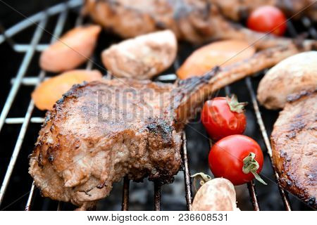 Appetizing juicy spare ribs and vegetables on barbecue grill, close up