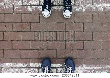 Legs In Sneakers On A Pedestrian Crossing Zebra Against Each Other