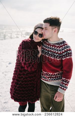 Stylish Young Couple Embracing On Quay At Winter