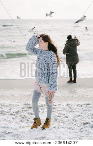 Stylish Girl In Merino Sweater On Winter Seashore, Boyfriend Standing Behind