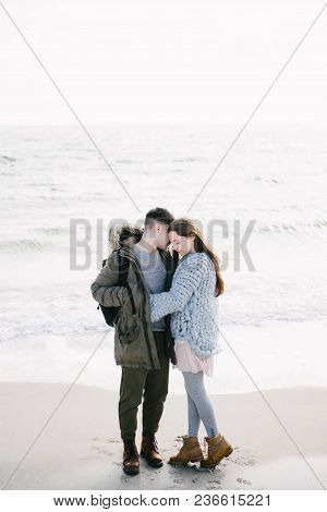 Young Tender Couple Embracing On Winter Seashore