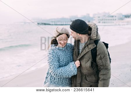 Smiling Young Couple Embracing And Walking On Winter Seashore