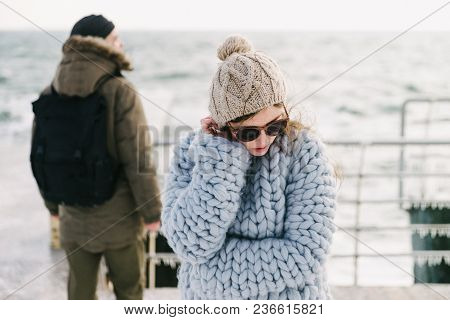 Stylish Girl In Sunglasses And Merino Sweater On Winter Quay, Boyfriend Standing Behind And Looking