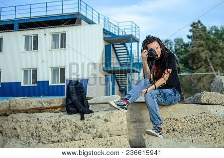 Girl Photographer With Dreadlocks Sitting On Stones With Camera In Hands