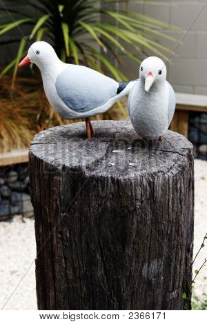 Bird statues sitting on a wooden block. poster