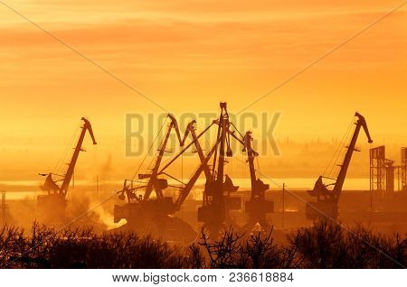 Construction Cranes In Sunset Or Sunrise. Industry. Orange Tinting.