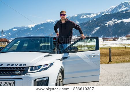 Austria, Alps - March 25, 2018: Young Man By The Latest Brand Of New White 2018 Range Rover Evoque.