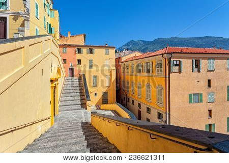 Stairs among colorful houses under blue sky in Menton - small town on French Riviera.